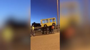 Four people dressed as a bus attempt to get across vehicle-only bridge