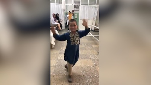 A kid celebrates after getting an artificial leg
