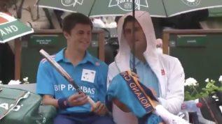 Djokovic shares umbrella with ball boy during rain delay